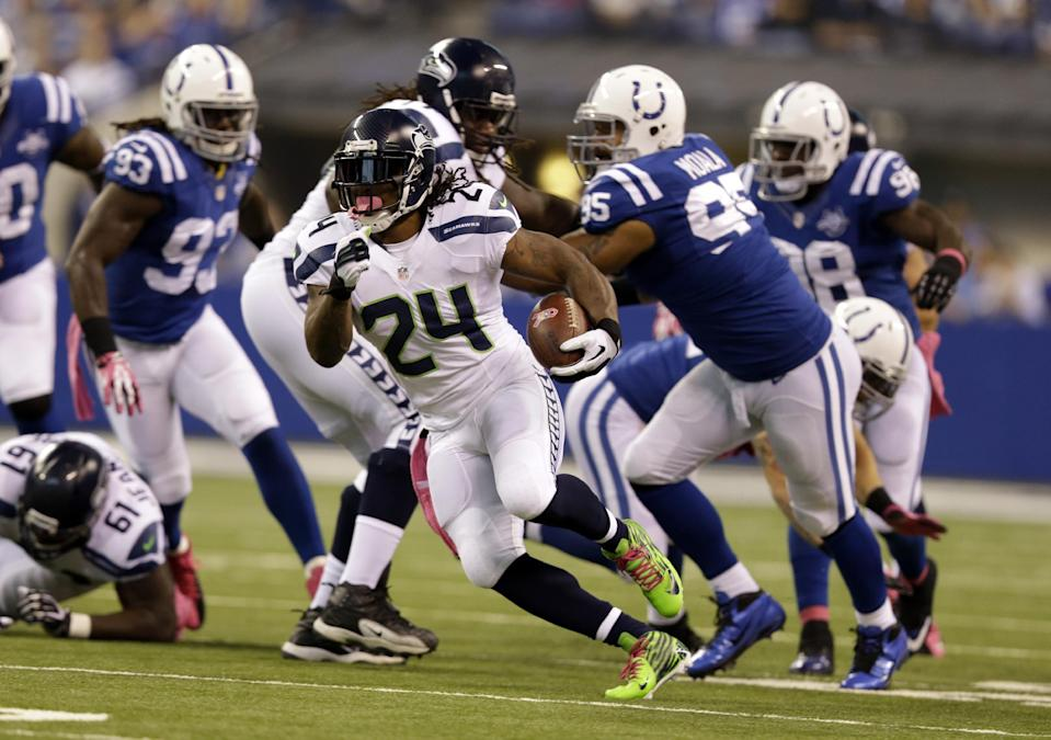 Seattle Seahawks running back Marshawn Lynch breaks through the Indianapolis Colts defense for a gain during the first half of an NFL football game in Indianapolis, Sunday, Oct. 6, 2013. (AP Photo/Michael Conroy)