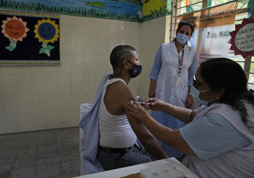 A health worker administers the vaccine for COVID-19 at a vaccination center set up at a government-run school in New Delhi, India, Tuesday, Sept. 21, 2021. India, the world's largest vaccine producer, will resume exports and donations of surplus coronavirus vaccines in October after halting them during a devastating surge in domestic infections in April, the health minister said Monday. (AP Photo/Manish Swarup)
