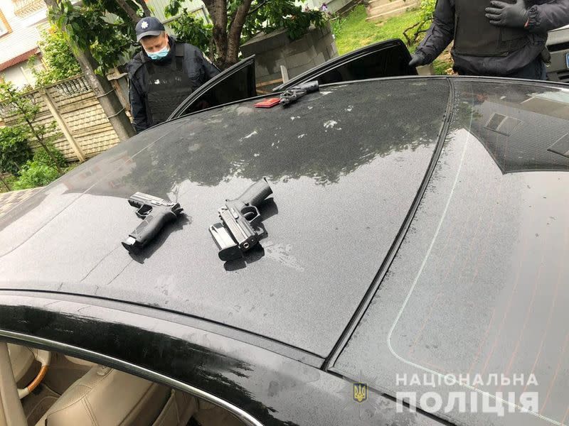 Police officers detain men suspected of taking part in a recent armed conflict in Brovary