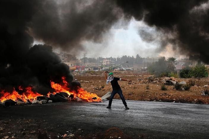 A Palestinian protester throws stones during clashes with Israeli security forces at the northern entrance of the West Bank town Al-Bireh, on the northern outskirts of Ramallah on October 26, 2015 (AFP Photo/Abbas Momani)