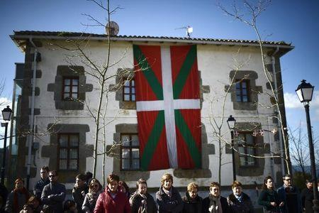 People stand in front of a large Ikurrina during a flag homage ceremony in Nabarniz