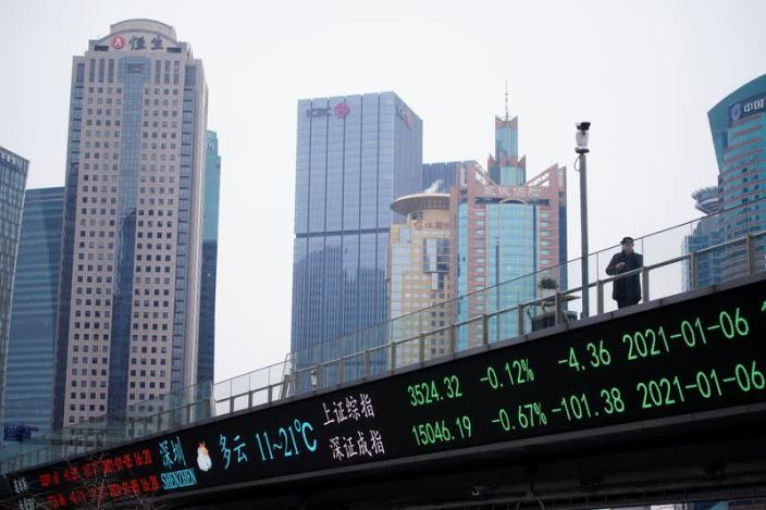 FILE PHOTO: A man wearing a mask, following the coronavirus disease (COVID-19) outbreak, stands on an overpass with an electronic board showing Shanghai and Shenzhen stock indexes, at the Lujiazui financial district in Shanghai
