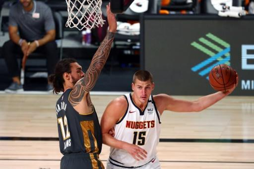 Nikola Jokic (right) drives against Steven Adams of the Oklahoma City Thunder on his way to a triple-double for the Denver Nuggets