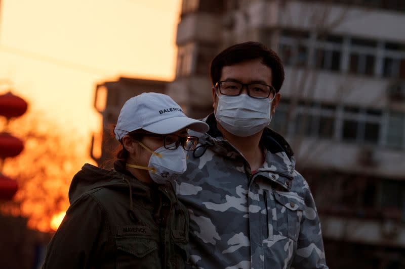 People wear face masks in a street in Beijing as the country is hit by an outbreak of the novel coronavirus