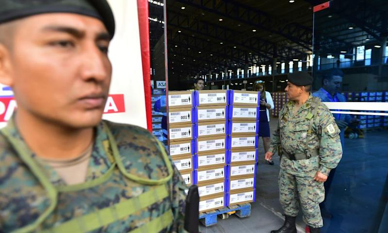 Soldiers stand guard as staff from Ecuador's national electoral council verify material before the vote.