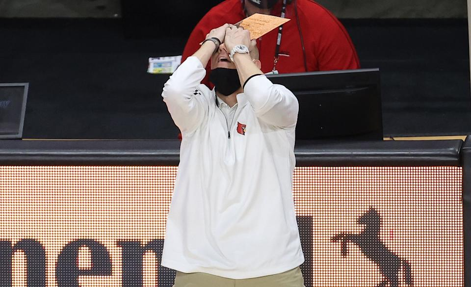 Chris Mack throws his head back and covers his face with his hands in reaction to a play that went against his team.