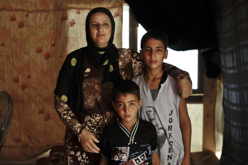 In this Wednesday, Sept. 11, 2013 photo, a Syrian woman poses for a portrait with her two sons inside their tent at a temporary refugee camp, in the eastern Lebanese town of al-Faour in the Bekaa valley, near the border with Syria. They are a few of Syria's refugees in Lebanon, driven out of their homes by a civil war that has killed over 100,000 and displaced millions. (AP Photo/Nariman El-Mofty)