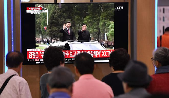 People in Seoul, South Korea, watch news coverage of Kim Jong-un and Xi Jinping's car parade in Pyongyang. Photo: AFP