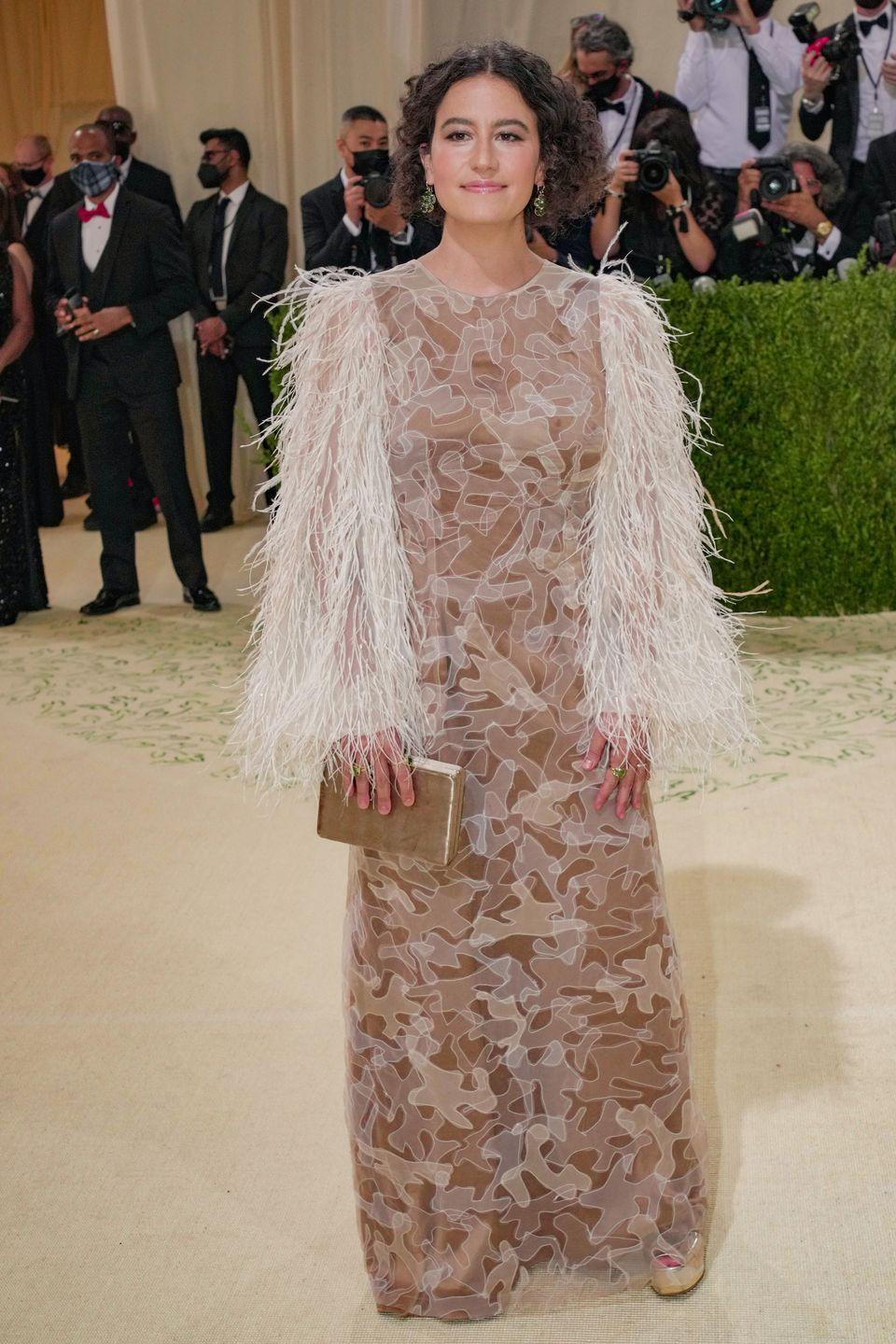 <p>Glazer looked chic in a patterned nude Aliette gown under a statement feathery sweater. Adding a pop of shimmer to the ensemble, she accessorized with a gold clutch and matching gold heels. </p>