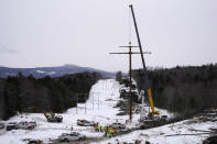 The first pole of Central Maine Power's controversial hydropower transmission corridor is prepared to be installed, Tuesday, Feb. 9, 2021, near The Forks, Maine. The pole was erected on an existing corridor that had been widened near Moxie Pond. (AP Photo/Robert F. Bukaty)