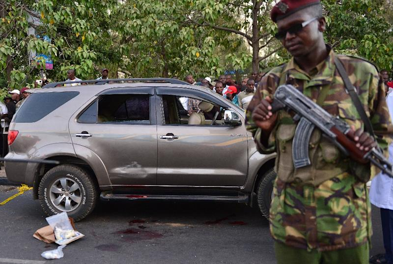 A police officer stands near the blood stained vehicle of prominent government MP  George Muchai, a member of Kenyan's governing Jubilee coalition, after  he was shot dead by gunmen early morning in Nairobi, on February 7, 2015