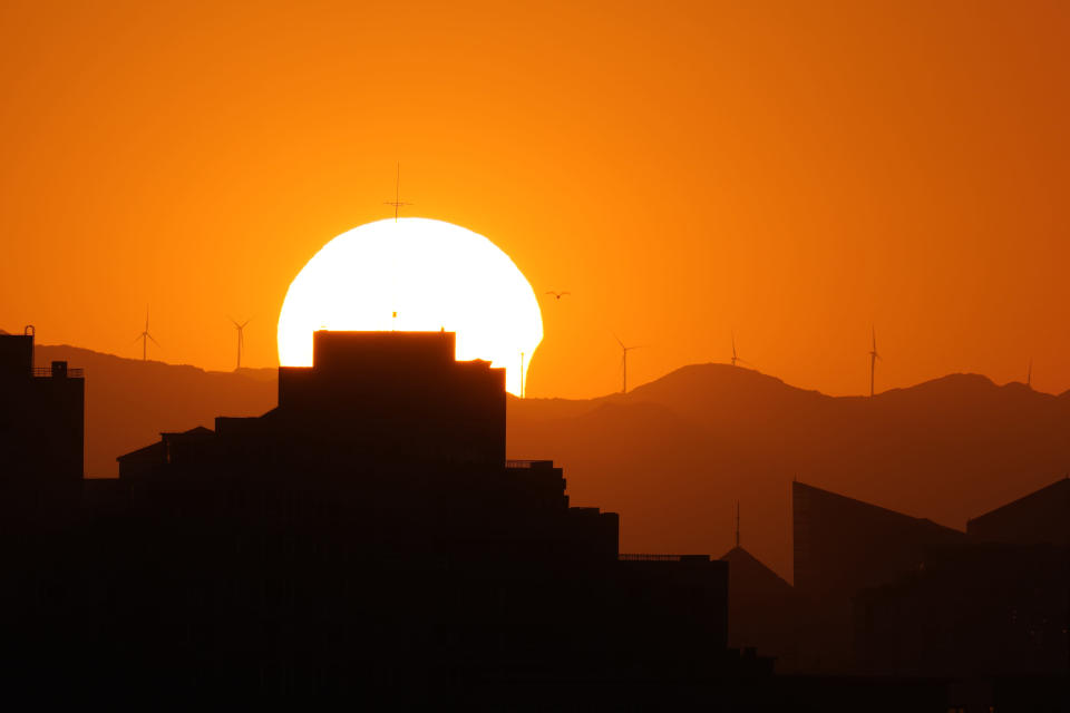 The sun is partially eclipsed as it sets over the horizon in Beijing on Thursday, June 10, 2021. (AP Photo/Ng Han Guan)