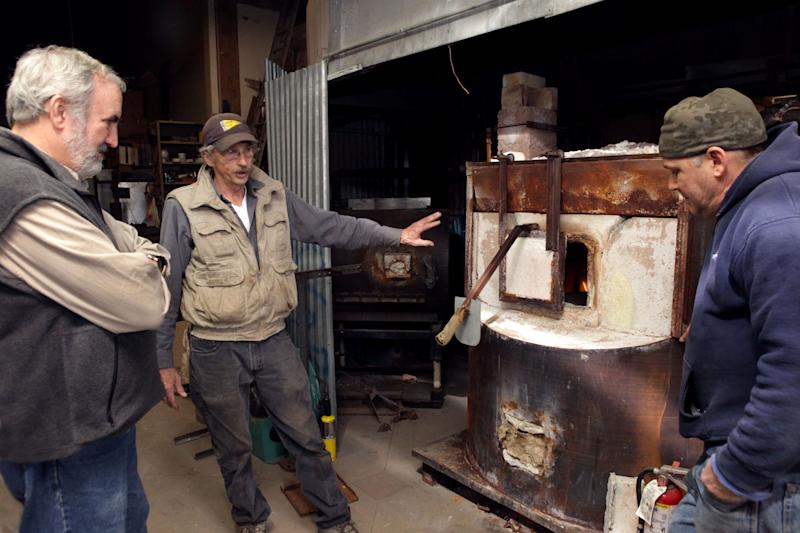This Dec. 3, 2012, photo provided by Craft Emergency Relief Fund (CERF+) Craig Nutt, left, of CERF+ is shown a damaged furnace at Pier Glass in the Red Hook neighborhood of Brooklyn, New York by artists Kevin Kutch and Kevin Scanlan, right. Scanlan is describing their attempt to dry out the furnace, which was inundated with salt water from Superstorm Sandy. (AP Photo/CERF+, George Hirose)