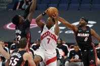 Toronto Raptors guard Kyle Lowry (7) goes to the basket between Miami Heat forward Bam Adebayo (13) and forward Maurice Harkless during the first half of an NBA preseason basketball game Friday, Dec. 18, 2020, in Tampa, Fla. The Raptors are playing their home games in Tampa as a result of Canada's strict travel regulations stemming from the coronavirus pandemic. (AP Photo/Chris O'Meara)
