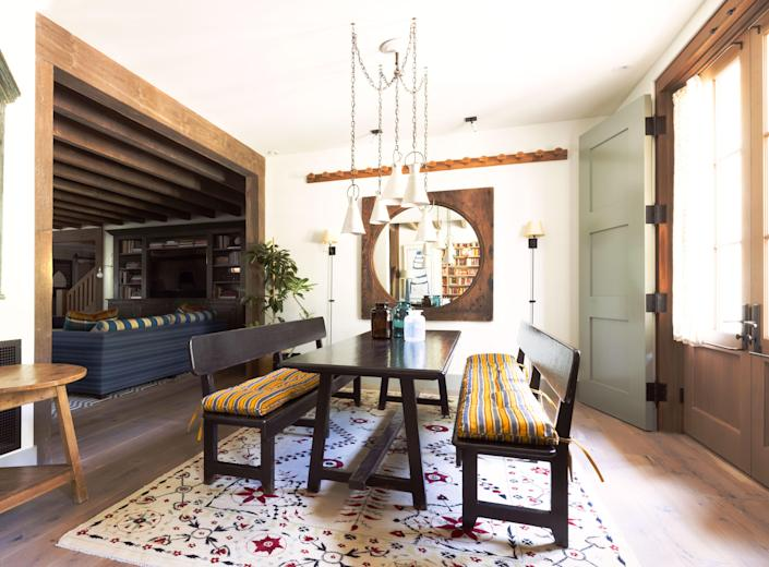 """Designer Virginia Davidson hired Los Angeles–based father-and-son carpentry team Lidio and Wilson Gutierrez and furniture finisher Ruben Moreno to craft the custom dining room table and benches. """"I have never felt anything so comfortable,"""" she says. The designs sit atop an embroidered rug by Penny Morrison. The ceramic pendant lights are by Natalie Page; the mirror is from Brenda Antin."""