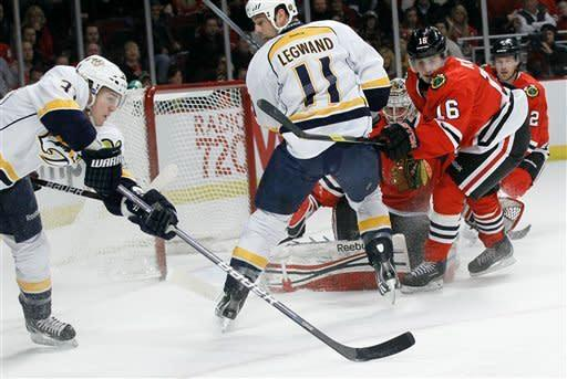 Nashville Predators left wing Colin Wilson, left, takes a shot as Nashville Predators center David Legwand (11) and Chicago Blackhawks goalie Corey Crawford, center, and teammates Marcus Kruger (16) and Duncan Keith (2) watch during the first period of an NHL hockey game Tuesday, Jan. 24, 2012, in Chicago. (AP Photo/Charles Rex Arbogast)