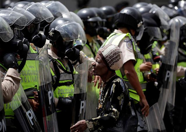 <p>Demonstrator stands next to riot police during rally against Venezuela's President Nicolas Maduro in Caracas, Venezuela May 1, 2017. (Photo: Marco Bello/Reuters) </p>