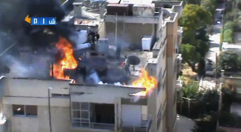 In this image taken from video obtained from the Shaam News Network, which has been authenticated based on its contents and other AP reporting, people try to extinguish a fire on the roof of a building, allegedly caused by shelling in Homs, Syria, Thursday, Oct. 31, 2013. President Bashar Assad's government met a key deadline in an ambitious plan to eliminate Syria's entire chemical weapons stockpile by mid-2014 and avoid international military action. (AP Photo/Shaam News Network via AP Video)