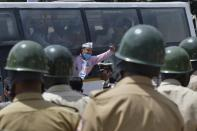 Police personnel stand guard as an activist from a farmers rights organisation gestures during a protest following the recent passing of agriculture bills in the Lok Sabha (lower house), in Bangalore on September 25, 2020. - Angry farmers took to the streets and blocked roads and railways across India on September 25, intensifying protests over major new farming legislation they say will benefit only big corporates. (Photo by Manjunath Kiran / AFP) (Photo by MANJUNATH KIRAN/AFP via Getty Images)