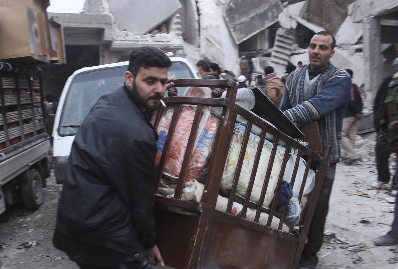 Residents collect belongings in an area damaged by what activists said was an air strike by forces loyal to Syria's President Assad, in Salehin