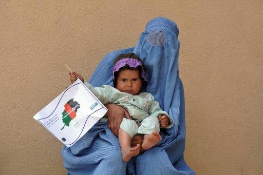 An Afghan woman holds a child in a tuberculosis section of the main hospital in Herat on April 9, 2012