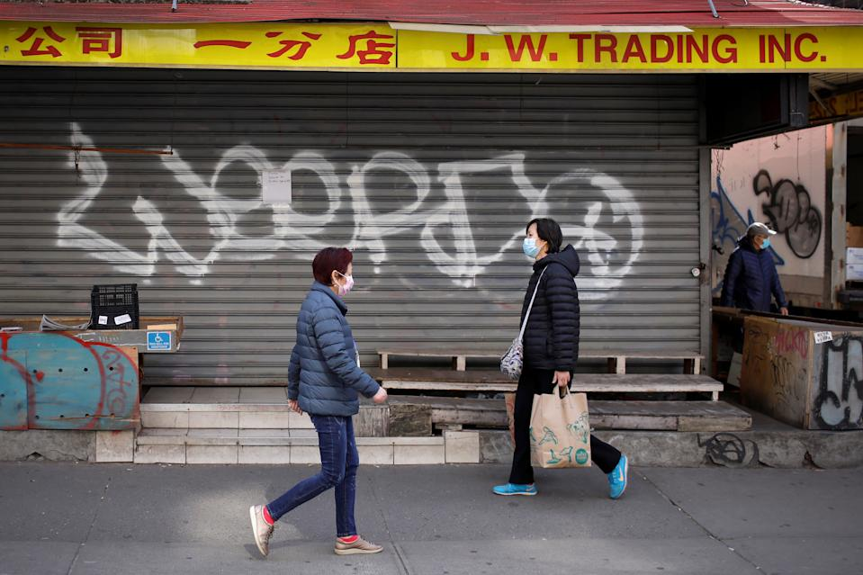 People in masks walk past a closed shop in the Chinatown neighborhood of Manhattan during the coronavirus outbreak in New York City, New York, U.S., March 18, 2020. REUTERS/Mike Segar