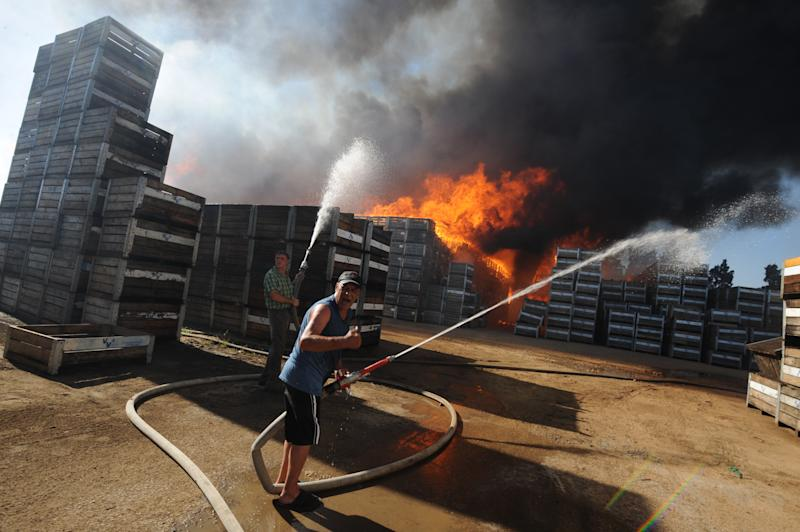 Farmers spray water as they try and save around 18,000 empty fruit containers from burning after being set alight by farm workers in Wolseley, South Africa, Wednesday, Nov. 14, 2012. Violent protests by farm workers have erupted in South Africa after weeks of unrest in the country's mining industry. Television images showed protesters overturn a police truck and set fires in the streets Wednesday in a town in South Africa's Western Cape. The workers have been protesting their wages, saying they want a minimum wage of $17 a day. Currently, workers make about half that amount a day. (AP Photo)