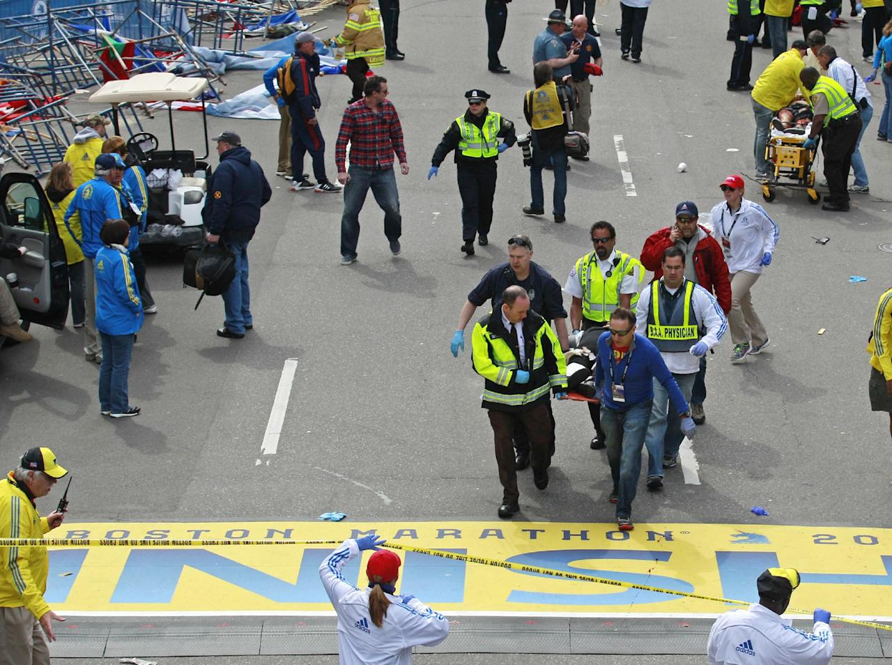 Medical workers wheel the injured across the finish line during the 2013 Boston Marathon following an explosion in Boston, Monday, April 15, 2013. Two explosions shattered the euphoria of the Boston Marathon finish line on Monday, sending authorities out on the course to carry off the injured while the stragglers were rerouted away from the smoking site of the blasts. (AP Photo/Charles Krupa)