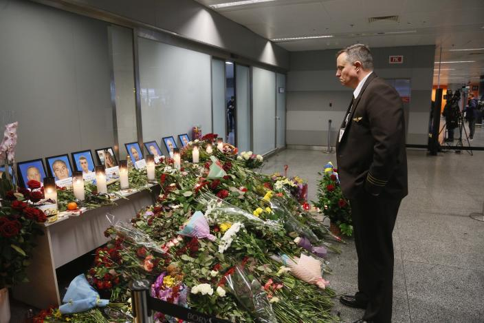 FILE - In this Jan. 10, 2020 file photo, an airport employee looks at a makeshift memorial inside Borispil international airport in Kyiv, Ukraine, for the flight crew of the Ukrainian 737-800 plane that crashed on the outskirts of Tehran. Iran's cabinet has created a compensation fund to pay the families of the 176 victims of the Ukrainian passenger plane that was shot down by Iranian forces outside Tehran last January, the president announced Wednesday, Dec. 30. (AP Photo/Efrem Lukatsky, File)