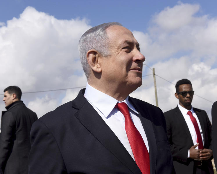Israeli Prime Minister Benjamin Netanyahu, center, surrounded by bodyguards, gets an overview of the West Bank Israeli settlement of Har Homa where he announced a new neighborhood is to be built, Thursday, Feb. 20, 2020. (Debbie Hill/Pool via AP)
