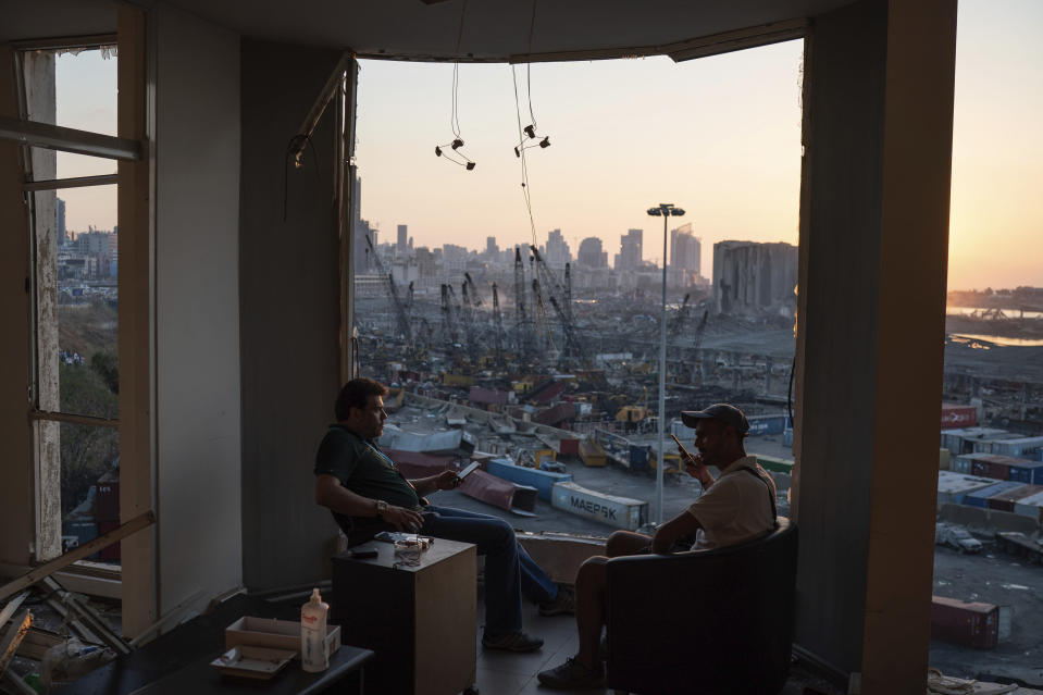 Two men sit on the destroyed balcony of a building facing the site of last week's massive explosion in the port of Beirut, Lebanon, Friday, Aug. 14, 2020. (AP Photo/Felipe Dana)