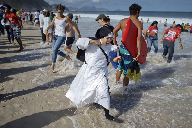 A nun reacts as the tide comes in fast on Copacabana beach in Rio de Janeiro, Brazil, Saturday, July 27, 2013. Pope Francis will preside over an evening vigil service on Copacabana beach that is expected to draw more than 1 million young people. (AP Photo/Victor R. Caivano)