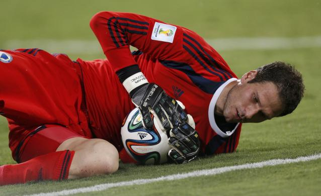 Bosnia's Asmir Begovic holds onto the ball as he lies on the ground during their 2014 World Cup Group F soccer match against Nigeria at the Pantanal arena in Cuiaba June 21, 2014. REUTERS/Ueslei Marcelino (BRAZIL - Tags: SOCCER SPORT WORLD CUP)