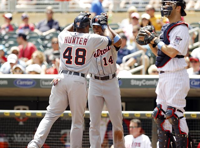 Detroit Tigers' Torii Hunter (48) is congratulated by Austin Jackson (14) after hitting a two-run home run against Minnesota Twins starting pitcher P.J. Walters as catcher Joe Mauer, right, looks on, during the first inning of a baseball game, Sunday, June 16, 2013, in Minneapolis. This was Hunter's 300th career home run. (AP Photo/Genevieve Ross)