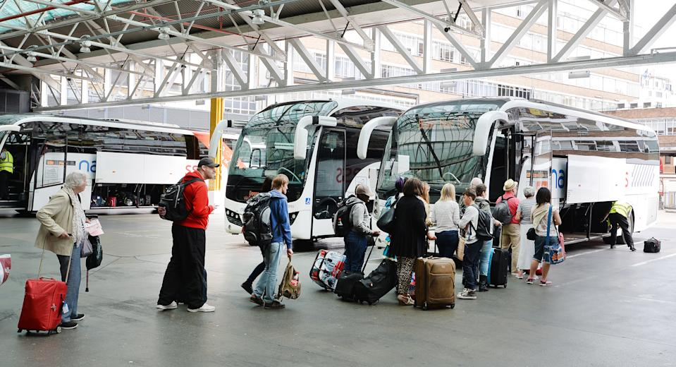 People board a National Express coach at the Victoria Coach Station, in central London.