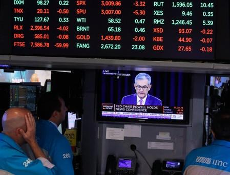 Traders look on as a screen shows Federal Reserve Chairman Jerome Powell's news conference after the U.S. Federal Reserve interest rates announcement on the floor of the New York Stock Exchange (NYSE) in New York