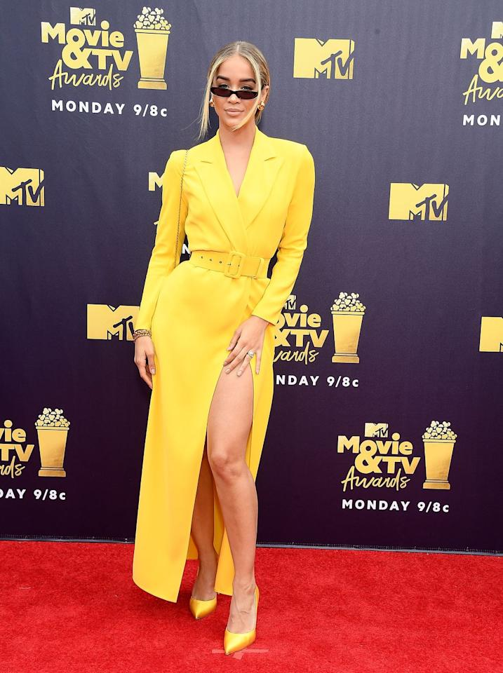 """<p>The """"Golden Barbie"""" wore a belted Alexander Terekhov dress with a high leg slit, but despite its bright yellow shade, her tiny sunglasses appeared to be the star of the show.</p>"""