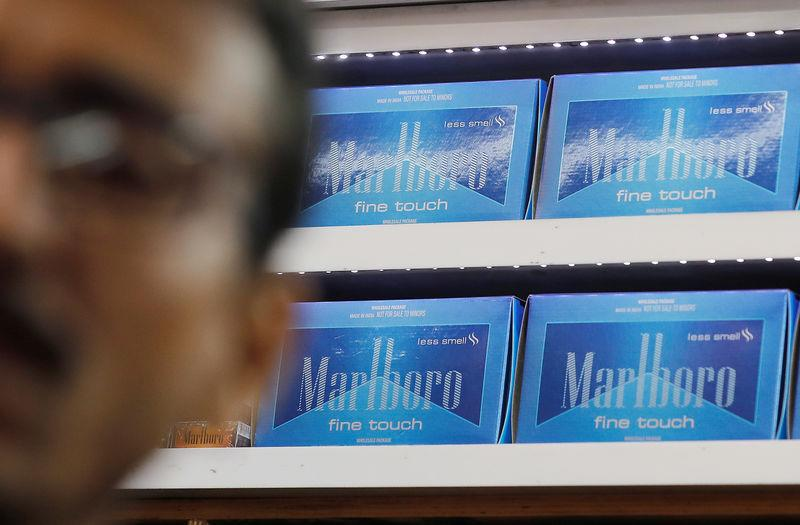 Marlboro cigarette packets are seen inside a stall as a man stands outside in New Delhi