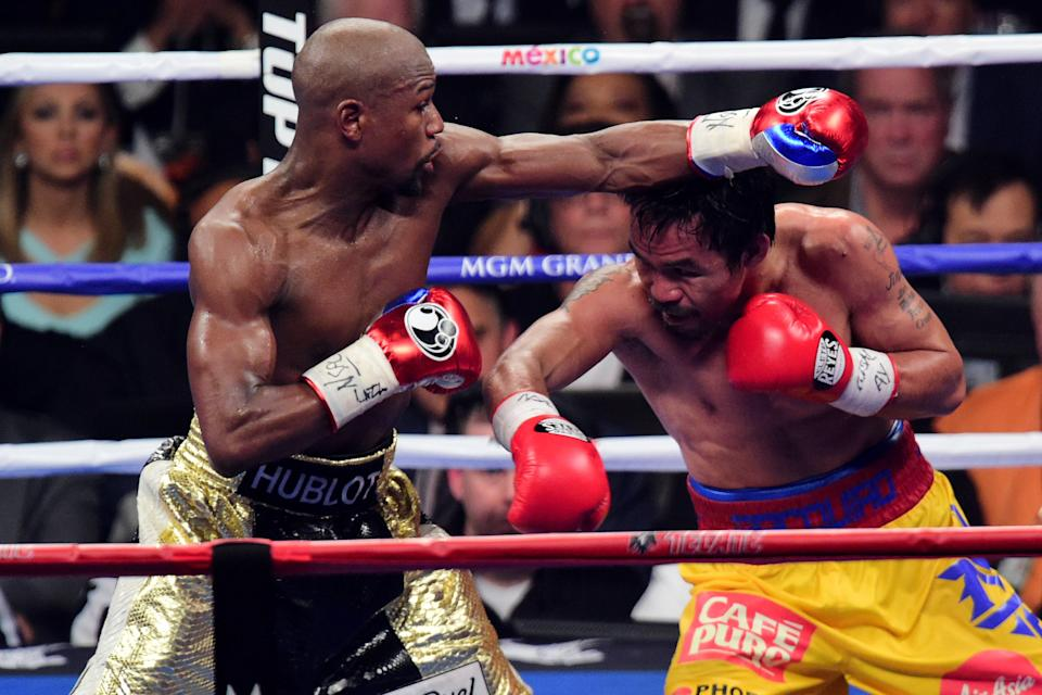May 2, 2015; Las Vegas, NV, USA; Floyd Mayweather (black/gold trunks) and Manny Pacquiao (yellow/red trunks) box during their world welterweight championship bout at MGM Grand Garden Arena. Mayweather won via unanimous decsion. Mandatory Credit: Joe Camporeale-USA TODAY Sports