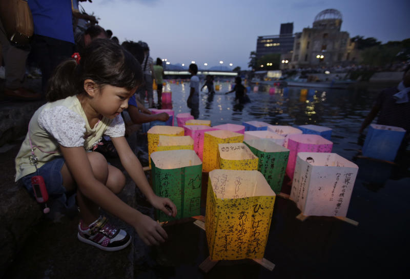 A girl releases a paper lantern for the repose of the soul of her great grandmother who died in the atomic bombing in the Motoyasu River with the backdrop of the Atomic Bomb Dome in Hiroshima, western Japan, Tuesday, Aug. 6, 2013. Japan marked the 68th anniversary Tuesday of the atomic bombing of Hiroshima with a somber ceremony to honor the dead and pledges to seek to eliminate nuclear weapons. (AP Photo/Shizuo Kambayashi)