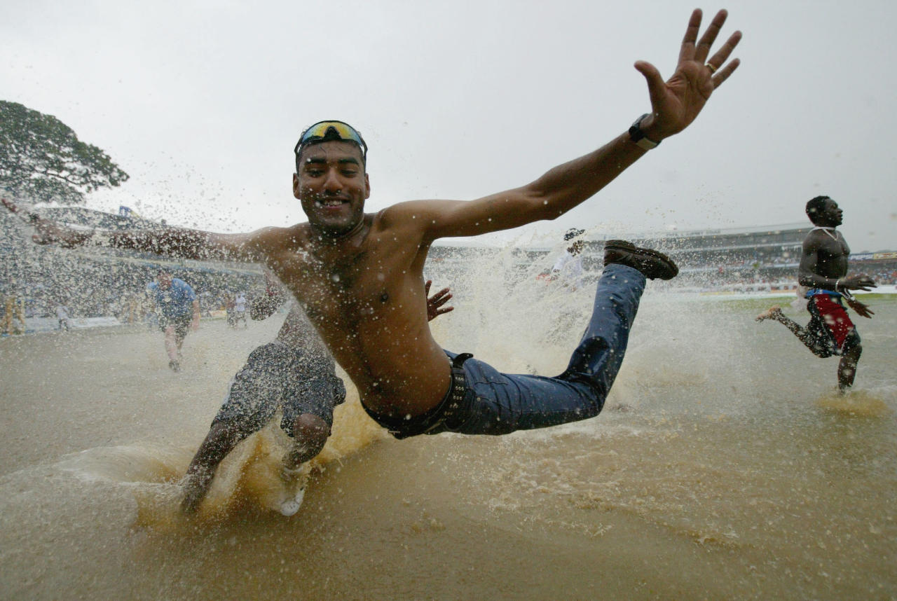 PORT OF SPAIN, TRINIDAD - APRIL 24:  A fan dives into the water as the pitch floods due to heavy rain during the 2nd One Day International at the Queens Park Oval, on April 24, 2004, in Port of Spain, Trinidad. (Photo by Clive Rose/Getty Images)