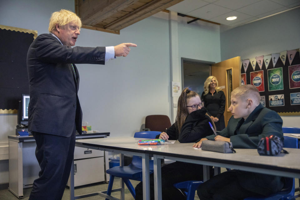 FILE - In this Wednesday, Aug. 26, 2020 file photo, Britain's Prime Minister Boris Johnson gestures during a visit to Castle Rock school on the pupils' first day back, in Coalville, East Midlands, England. Johnson is announcing plans Monday, Feb. 22, 2021 to ease restrictions in increments, starting by reopening schools in England on March 8. People will be allowed to meet one friend or relative for a chat or picnic outdoors from the same day. Three weeks later, people will be able to meet outdoors in groups of up to six outdoors. But restaurants, pubs, gyms and hairdressers are likely to remain closed until at least April. (Jack Hill/Pool Photo via AP, File)