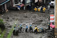 Rescuers in Japan's Atami wade through streams of murky water and move large blocks of timber and other detritus out of the way