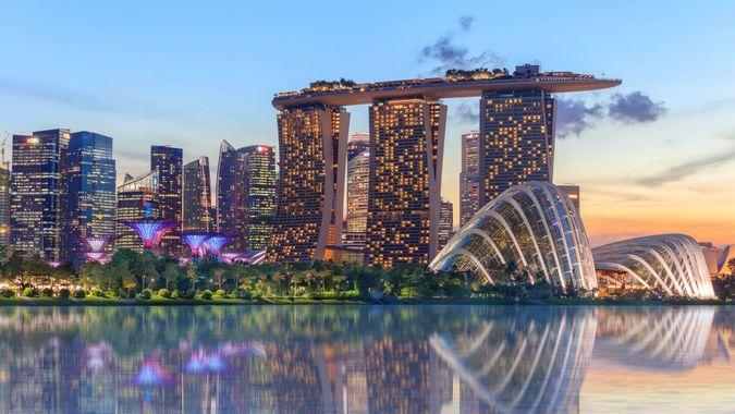 Singapore, Republic of Singapore - May 4, 2016: Supertree grove, Cloud garden greenhouse and Marina Bay Sands hotel reflecting in water at dusk with glowing lights.