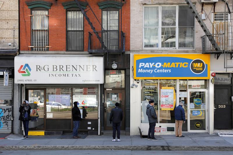 People queue to enter Payomatic, a business that offers check cashing, as unemployment claim figures were released, during the coronavirus disease (COVID-19) outbreak in Manhattan, New York City, New York, U.S., April 2, 2020. REUTERS/Andrew Kelly