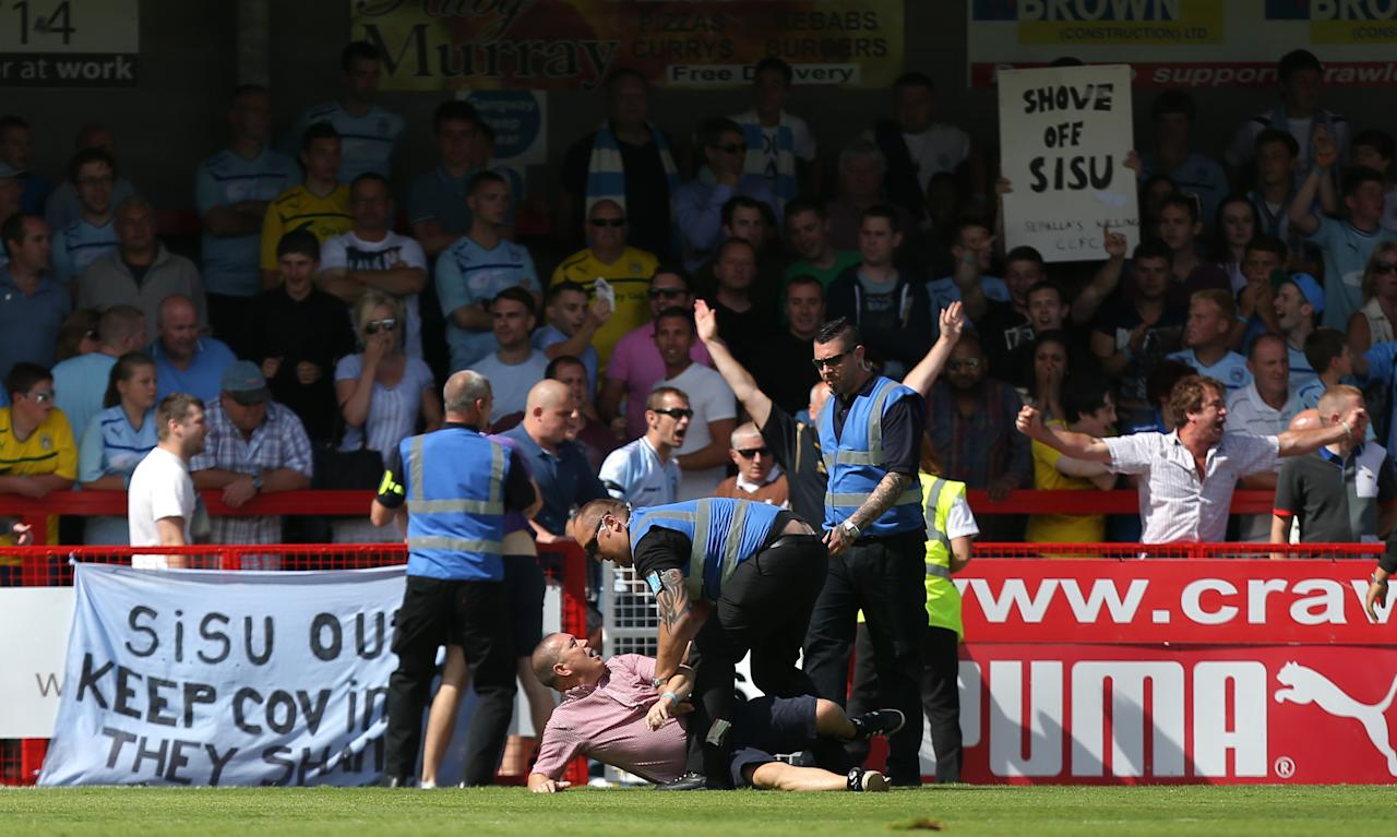A Coventry City fans is restrained by stewards after running onto the pitch during the Sky Bet League One match at Broadfield Stadium, Crawley.