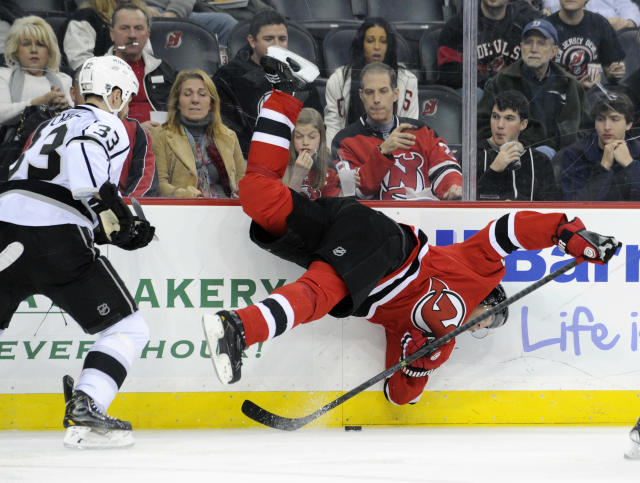 New Jersey Devils' Jaromir Jagr, right, of the Czech Republic, is sent flying on a check by Los Angeles Kings' Willie Mitchell during the second period of an NHL hockey game Friday, Nov. 15, 2013, in Newark, N.J. (AP Photo/Bill Kostroun)