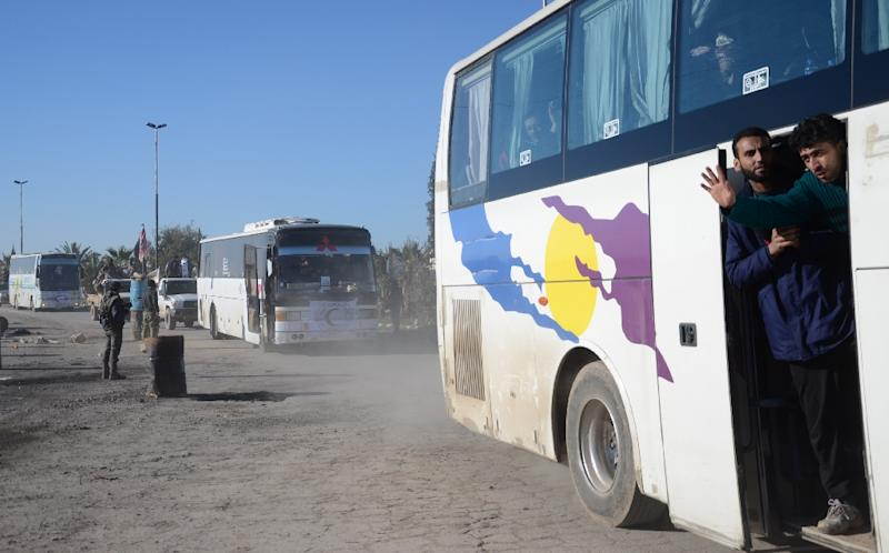 Syrians who were evacuated from Waer, the last opposition-held district of Homs, arrive in the northern Syrian town of al-Bab on March 19, 2017, under a Russian-supervised deal to bring Syria's third city under full government control