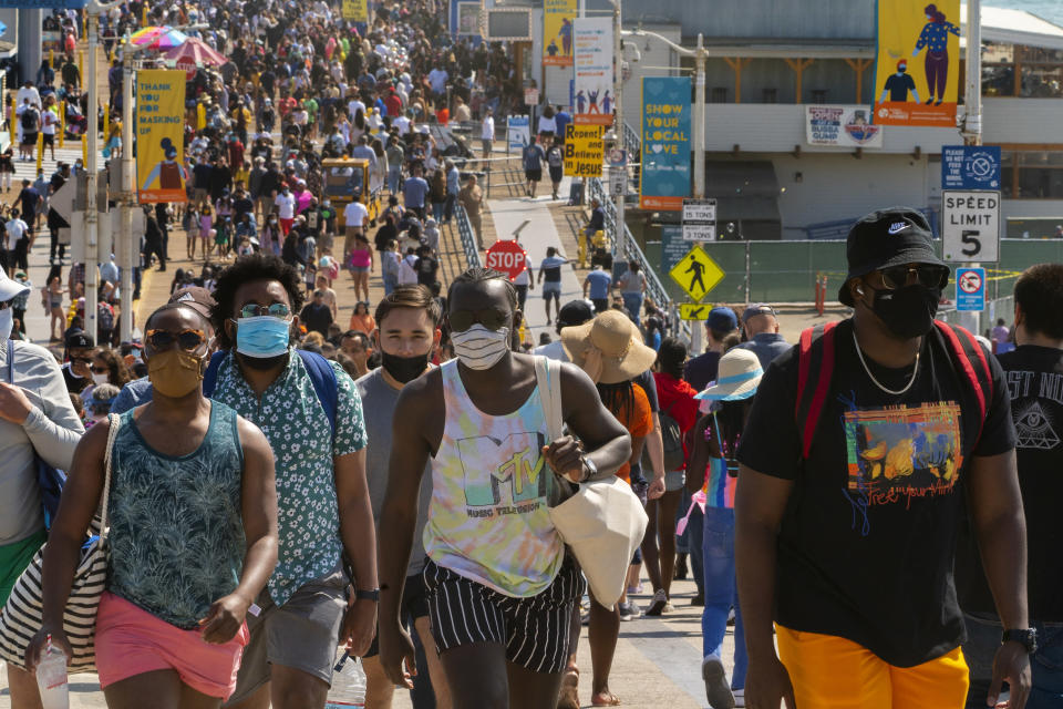 FILE - In this Saturday, May 29, 2021, file photo, people crowd the Santa Monica Pier in Santa Monica, Calif. Californians headed to campgrounds, beaches and restaurants over the long holiday weekend as the state prepared to shed some of its coronavirus rules. (AP Photo/Damian Dovarganes, File)