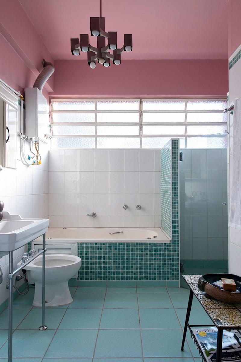 The tilework in the bathroom is part of the original design. Juliana refreshed the space with pink paint and a new light fixture.